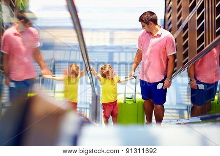 Happy Family Moving On Escalator, With Boarding Pass In Hands