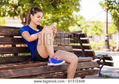 Runner Texting On A Park Bench