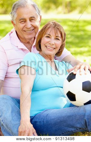 Senior Hispanic Couple Relaxing In Park With Football