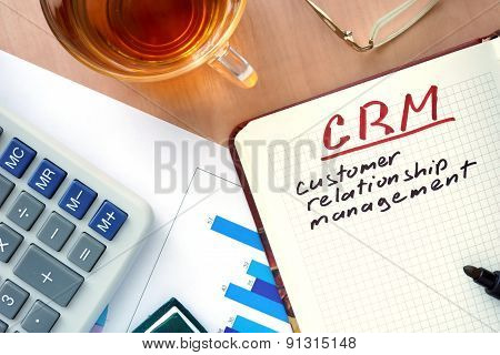 Notepad with word CRM customer relationship management concept.