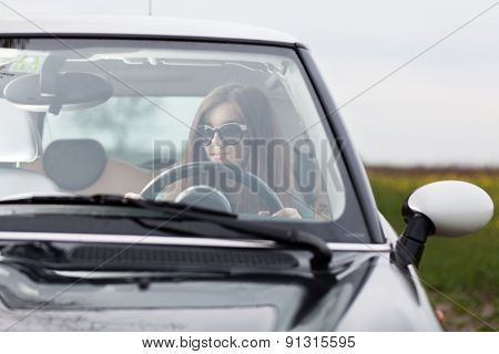 Young beuatiful woman driving a car.