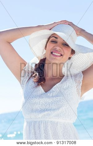 Pretty brunette wearing sunhat and looking at camera at the beach