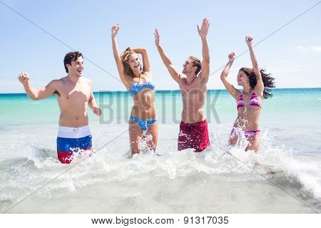 Happy friends having fun in the water together at the beach