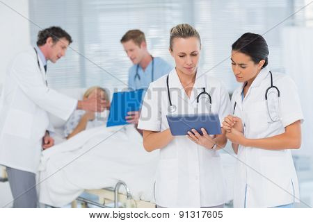 Doctors looking at clipboard while theirs colleagues speaks with patient in the hospital