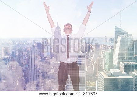 Smiling businessman cheering with his hands up against city skyline