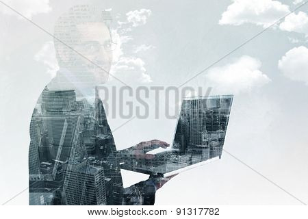 Smiling businessman using a laptop against new york skyline