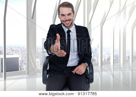 Smiling businessman on an chair office offering handshake against room with large window looking on city