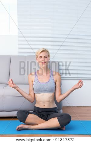 Fit blonde woman meditating on exercise mat