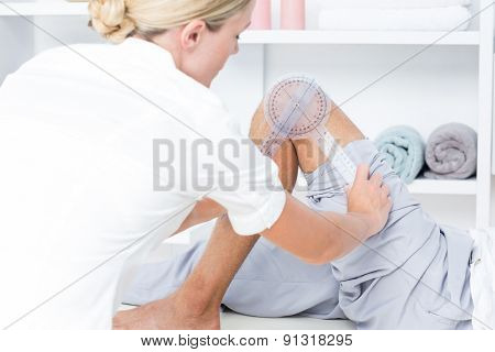 Doctor examining man leg with tool in medical office