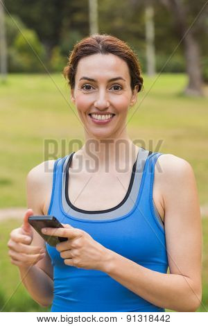 Pretty brunette using smartphone on a sunny day