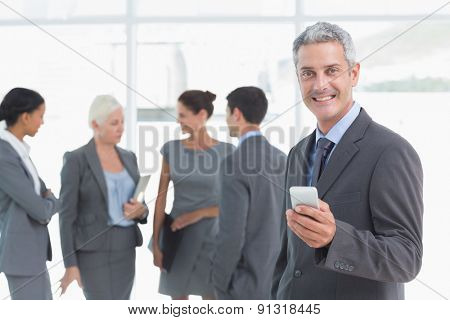 Businessman using mobile phone with colleagues behind in office