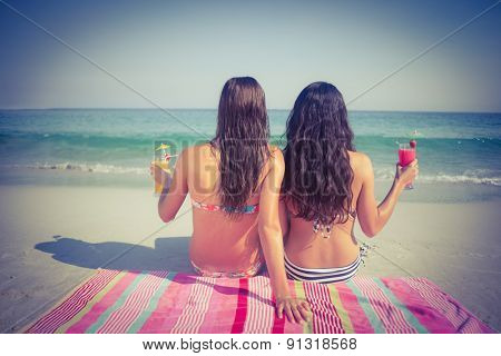 Two friends in swimsuits at the beach on sunny day