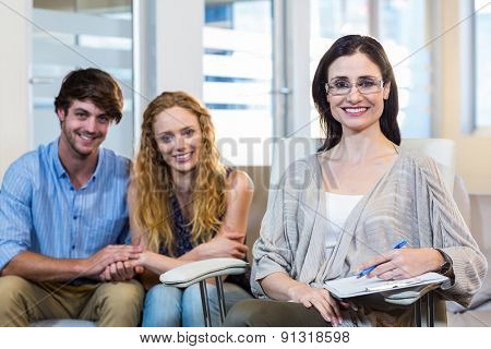 Psychologist and happy couple smiling at camera in the office