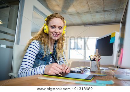 Smiling businesswoman sitting at her desk and listening music in the office