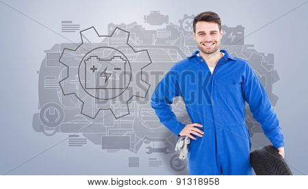 Smiling male mechanic holding tire against grey vignette