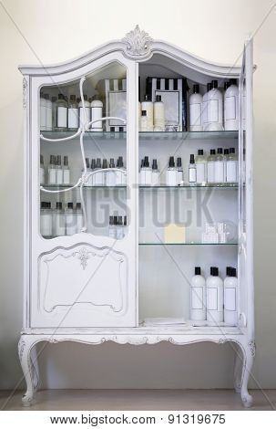 Old style, white baroq cabinet with bottles