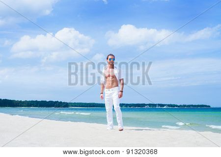 Young and handsome man on a summer beach
