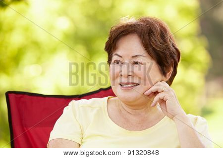 Senior Asian woman sitting outdoors
