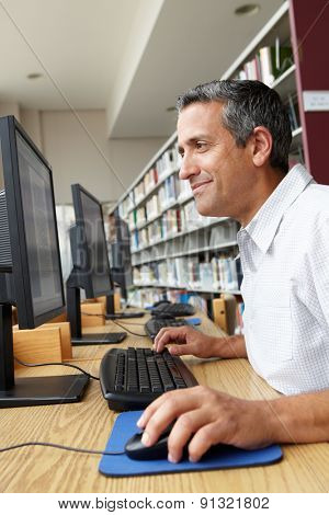 Man working on computer in library