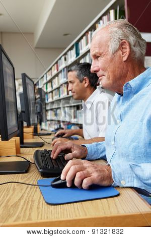 Men working on computers in library