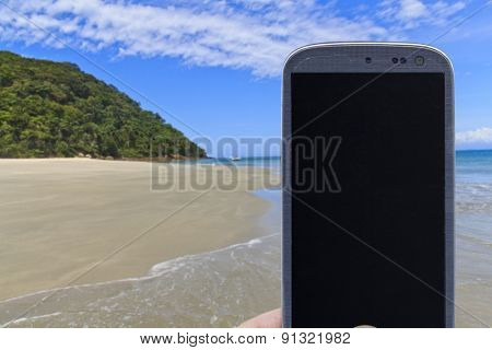 Smatrphone and a landscape. Idea of digital detox, taking shots, accessing apps, Internet, blogs and others. The blur image is beach at As ilhas in Barra do Sahy, Sao Sebastiao, Sao Paulo - Brazil