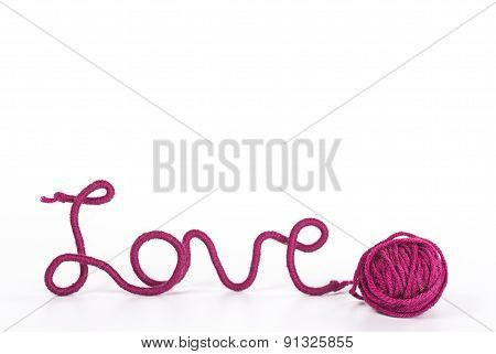 word love of red thread and ball of wool isolated