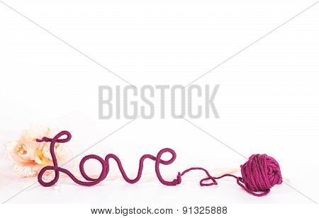 isolated word love of red thread and ball of wool