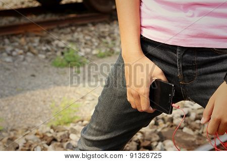 Women Wearing Jeans Holding A Cell Phone.