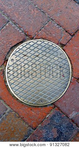 Manhole Cover On A Brick Road