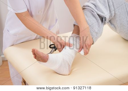 Woman Tying Bandage On Patient's Foot