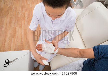 Female Doctor Bandaging Patient's Hand