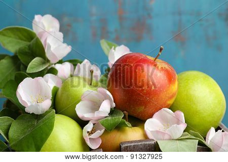 Fresh apples with apple blossom, on blue wooden background