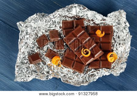Chocolate with orange peels in foil on wooden table, top view