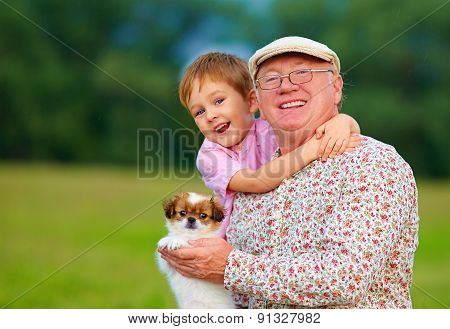 Portrait Of Happy Grandpa, Grandson And Puppy