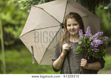 Portrait of teen girl with an umbrella and a bouquet of lilacs.