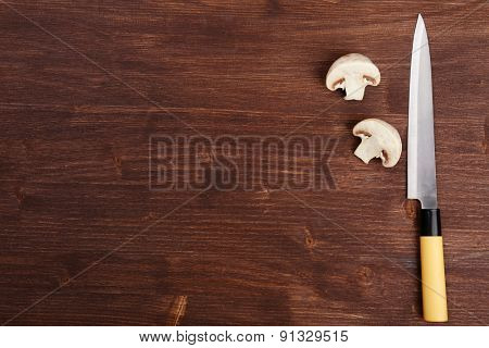 Halves of mushroom with knife on wooden background