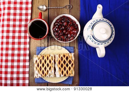 Baking, tea and jam on wooden table top view