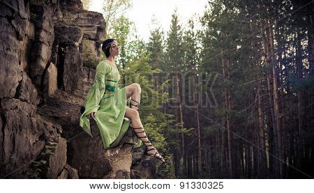 Elf Woman Is Sitting On The Rocks. Forest On The Background.
