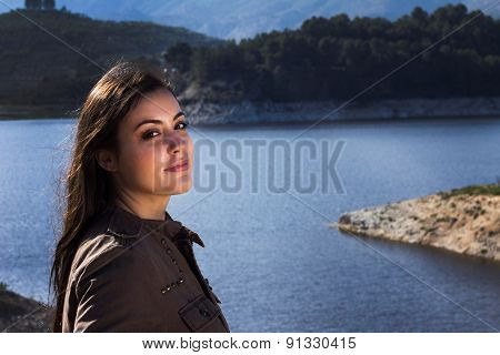 Girl Standing In Front Of A Lake With Mountains In The Backgroun