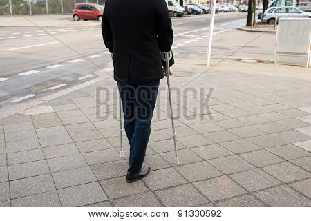Man Walking On Street Using Crutches