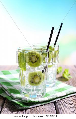 Glasses of cocktails on wooden table on bright blurred background