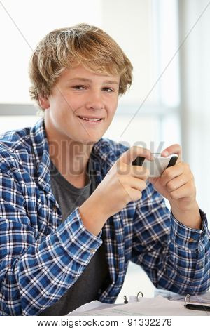 Teenage boy with phone in class