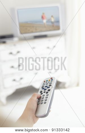 Young Girl Holding Television Remote Control In Bedroom