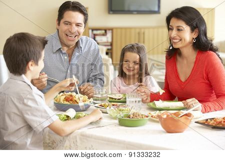 Young Hispanic Family Enjoying Meal At Home