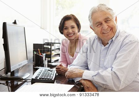 Senior Hispanic couple working on computer at home