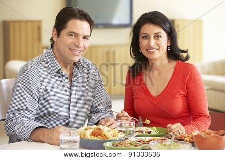 Young Hispanic Couple Enjoying Meal At Home