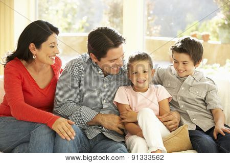 Young Hispanic Family Relaxing On Sofa At Home