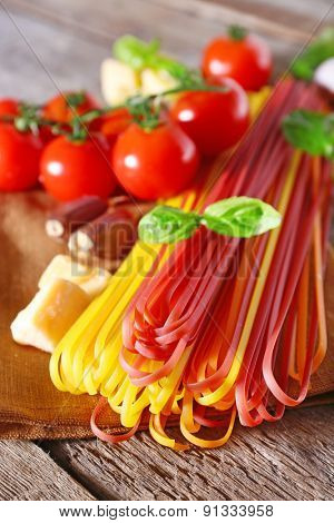 Pasta with cherry tomatoes and other ingredients on wooden table background