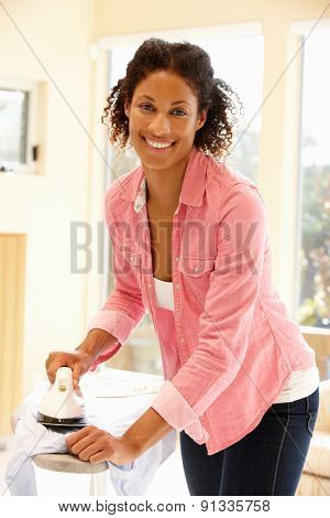 Mixed race woman ironing