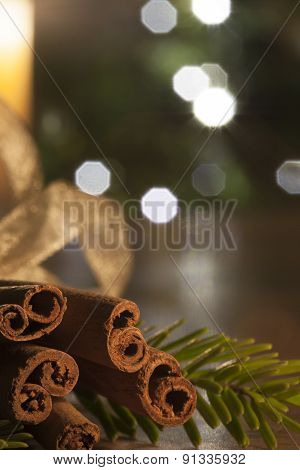 Cinnamon And A Lit Candle On A Wooden Table Infront Of A Christm